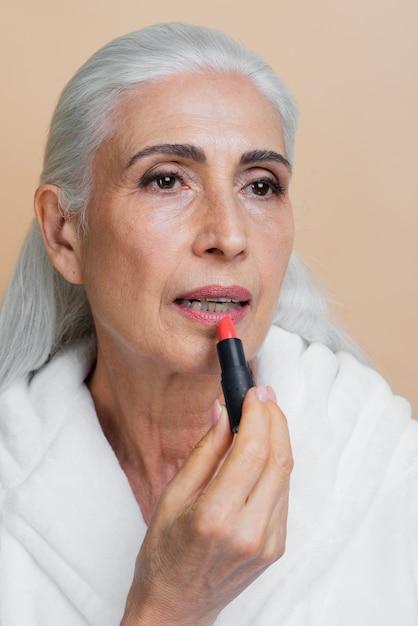 Linda mulher sênior aplicando batom Foto gratuita