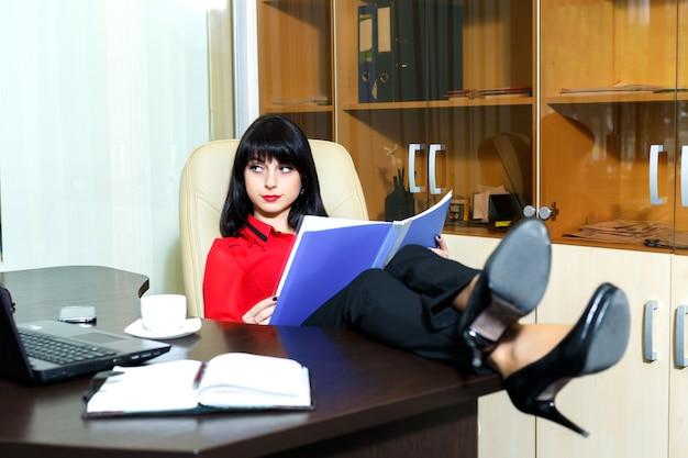 Linda mulher séria lendo um documentos na mesa em um escritório Foto Premium