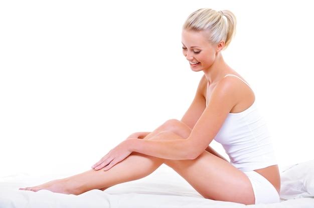 Linda mulher sorridente acariciando suas belas pernas, sentada na cama branca Foto gratuita