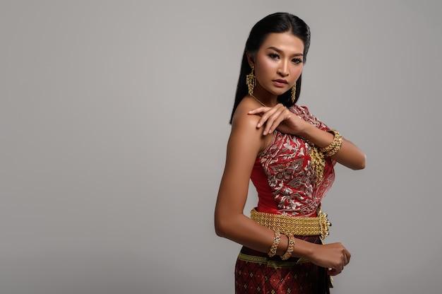 Linda mulher tailandesa com vestido tailandês e olhando para o lado Foto gratuita