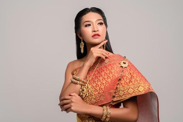 Linda mulher tailandesa com vestido tailandês e olhando para o topo Foto gratuita
