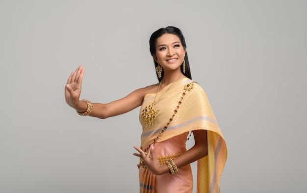Linda mulher tailandesa usando vestido tailandês e dança tailandesa Foto gratuita