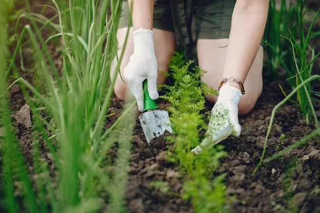 Linda mulher trabalha em um jardim perto da casa Foto gratuita