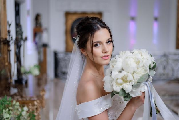 Linda noiva caucasiana morena está segurando o buquê de peônias brancas e olhando direto interior Foto gratuita