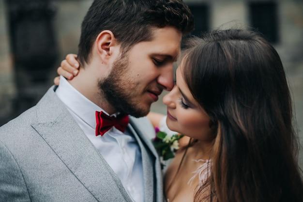 Linda noiva e noivo abraçando e beijando no dia do casamento ao ar livre Foto Premium