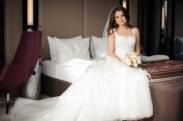 Linda noiva sentada na cama com uma flores Foto Premium