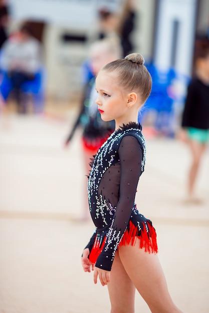 Linda pequena ginasta treinamento no tapete e pronto para competições Foto Premium