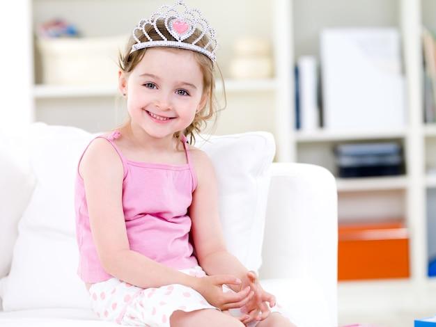 Linda princesinha linda em coroa com um sorriso sentada no sofá Foto gratuita