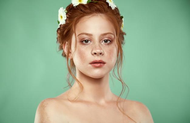 Linda ruiva positiva com uma coroa de camomila na cabeça Foto Premium