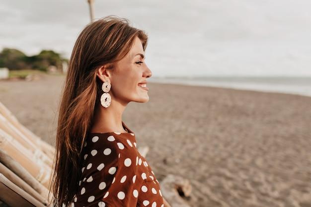 Linda senhora com sorriso gentil estrangeiro olhando para o oceano com sorriso romântico sob a luz do sol Foto gratuita