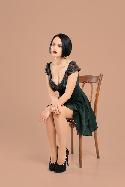 Linda senhora de vestido curto, sentado na cadeira em estúdio com fundo bege Foto Premium
