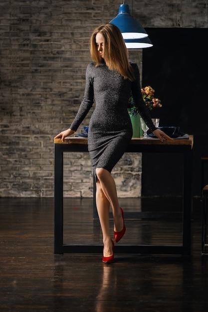 Linda senhora ib vestido encostado na mesa com o joelho dobrado em sapatos de verniz vermelho, olhando para o chão Foto Premium