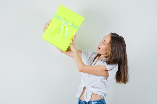 Linda senhora levantando caixa de presente em blusa branca, calça jeans, vista frontal. Foto gratuita