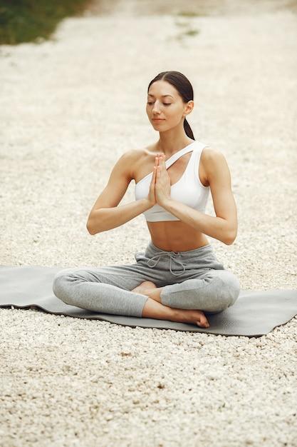 Linda senhora treinando em uma praia de verão. morena fazendo ioga. garota em um traje esportivo. Foto gratuita