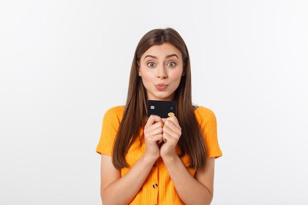 Linda sorridente confiante garota mostrando cartão preto na mão, isolado sobre o branco. Foto Premium
