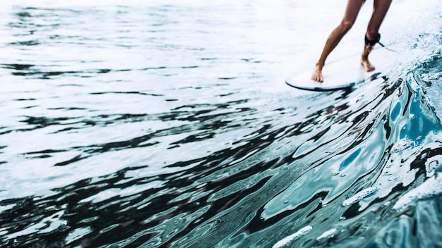 Linda surfista montando em uma placa Foto gratuita