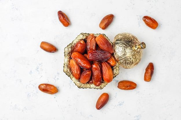 Linda tigela cheia de frutas data simbolizando o ramadã, vista superior Foto gratuita