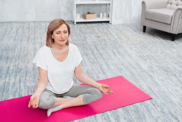 Linda velha meditando sobre tapete de ioga em casa Foto gratuita
