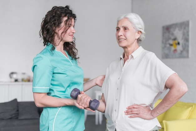 Linda velha senhora está fazendo exercício com halteres com a ajuda de fisioterapeuta Foto gratuita