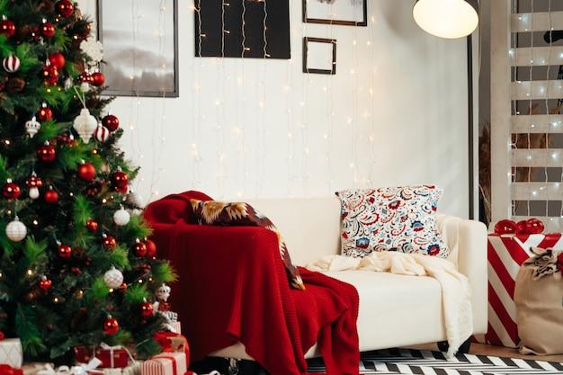 Lindamente decorado, sala de natal com abeto e sofá branco Foto Premium