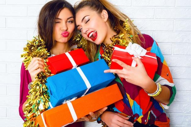Lindas amigas felizes e sorridentes segurando presentes e presentes para festas. vestindo roupas da moda e enfeites dourados Foto gratuita