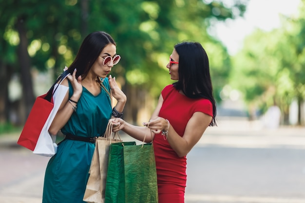 Lindas fêmeas felizes em óculos de sol, olhando para sacolas andando na rua Foto Premium