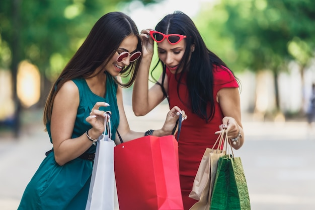 Lindas fêmeas felizes em óculos de sol, olhando para sacos de compras, andando na rua. Foto Premium