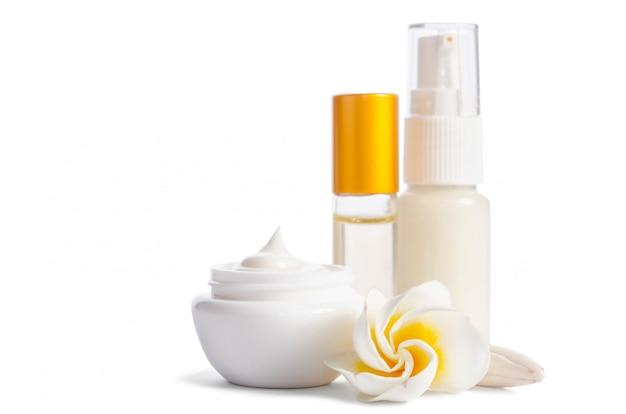 Lindas flores e frascos com creme para a pele natural, isolado no branco Foto Premium