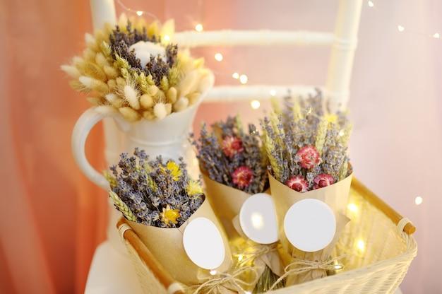 Lindas flores secas em caixas de papel com luzes no fundo Foto Premium