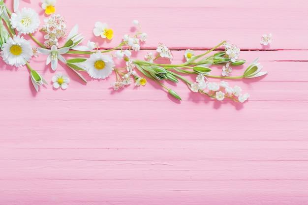 Lindas flores sobre fundo rosa de madeira Foto Premium
