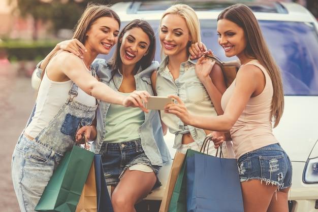 Lindas garotas elegantes estão fazendo selfie usando telefone inteligente. Foto Premium
