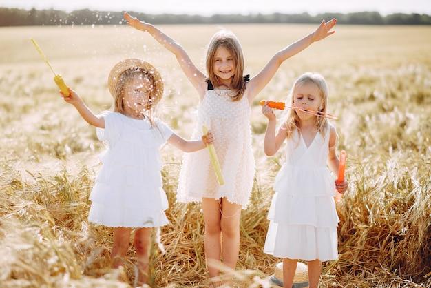 Lindas garotas se divertem em um campo de outono Foto gratuita