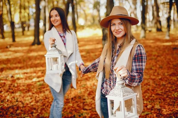 Lindas garotas se divertem em um parque de outono Foto gratuita