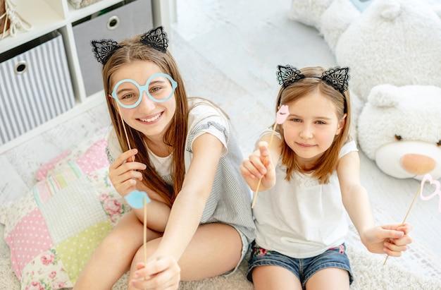 Lindas garotas se divertindo com óculos e lábios em palitos na sala de jogos Foto Premium