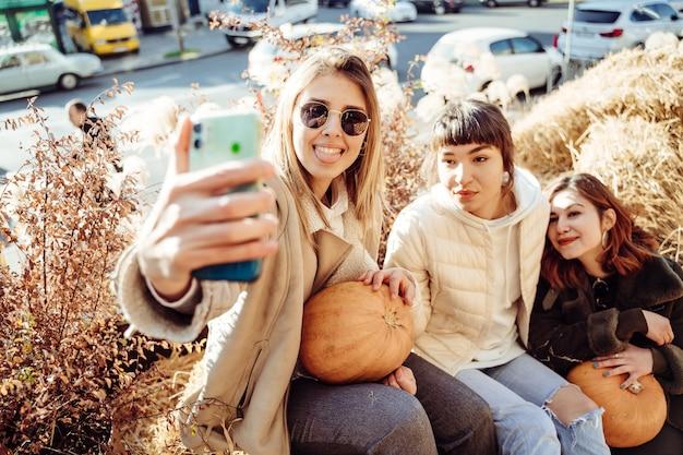 Lindas garotas sentadas em palheiros tirar uma selfie Foto gratuita