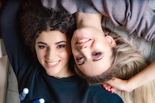 Lindas irmãs em suéteres quentes estavam no chão do estúdio e sorriam. fechar-se Foto Premium