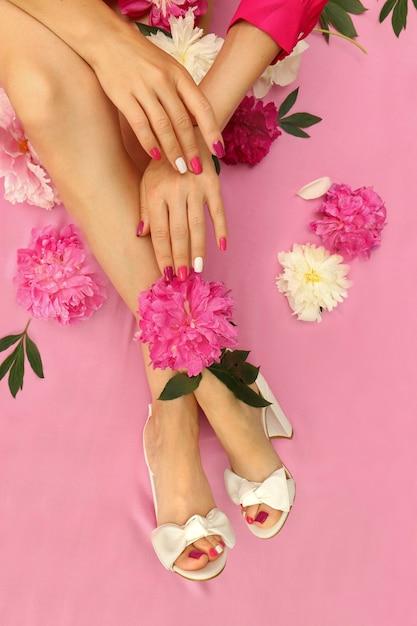 Lindas mãos de mulher com manicure e pés com peônias em sandálias brancas e com pedicure multicolor nas unhas. Foto Premium