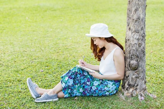 Lindas mãos femininas asiáticas com uma caneta escrevendo caderno e ela estava sentada na grama do lado de fora Foto Premium