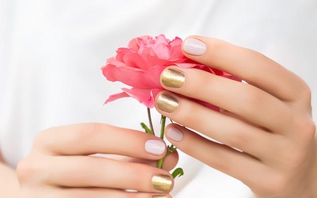 Lindas mãos femininas com design dourado e rosa perfeito prendem flor rosa fresca Foto gratuita