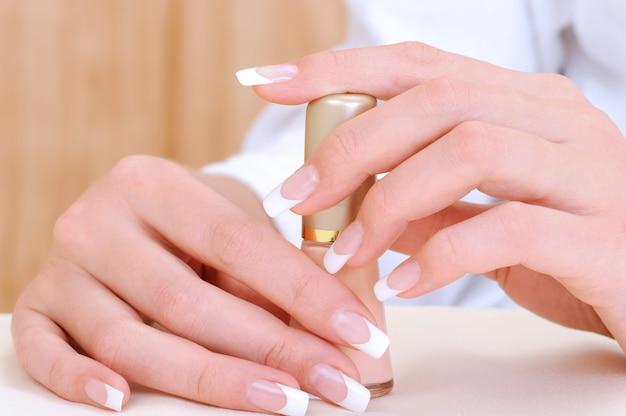 Lindas mãos femininas com manicure francesa de beleza segurando esmalte de garrafa Foto gratuita