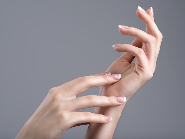 Lindas mãos femininas com manicure francesa nas unhas Foto gratuita