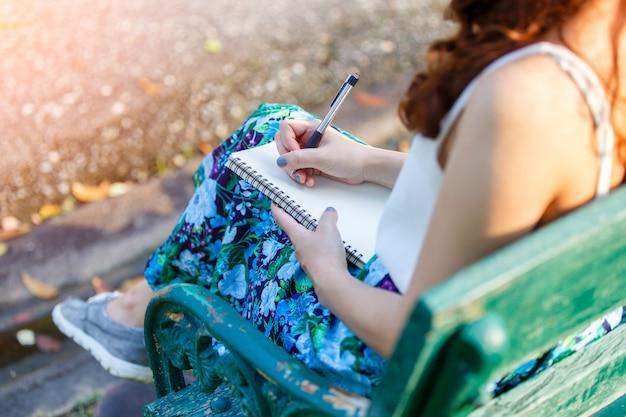 Lindas mulheres asiáticas com caneta escrevendo notebook e sentado Foto Premium