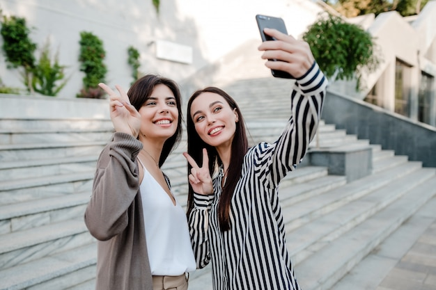 Lindas mulheres casuais fazendo selfie ao ar livre na cidade Foto Premium