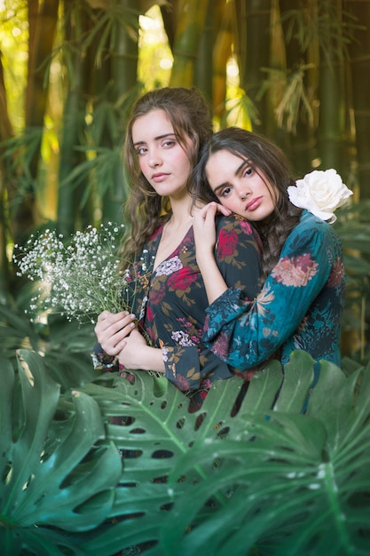 Lindas mulheres cercadas por folhas de monstera Foto gratuita