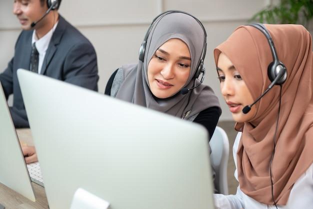 Lindas mulheres muçulmanas asiáticas trabalhando no escritório do call center Foto Premium