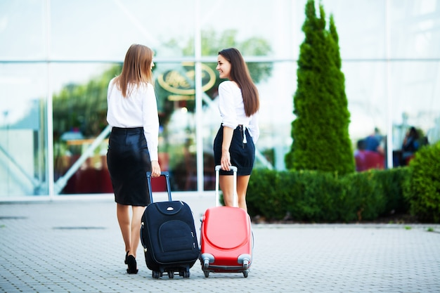 Lindas mulheres que gostam de viajar com malas perto do aeroporto Foto Premium