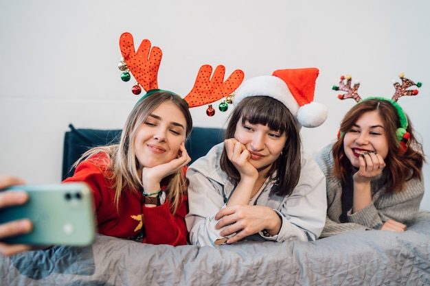 Lindas mulheres sorridentes se divertindo e tirando selfies Foto gratuita