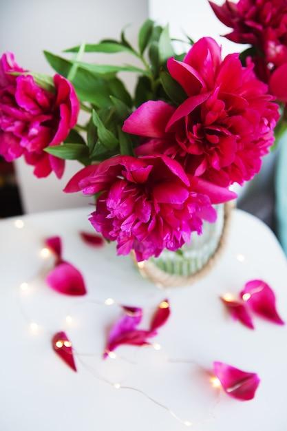 Lindas peônias rosa perto da janela, pétalas se esfarelam em cima da mesa com luzes Foto Premium