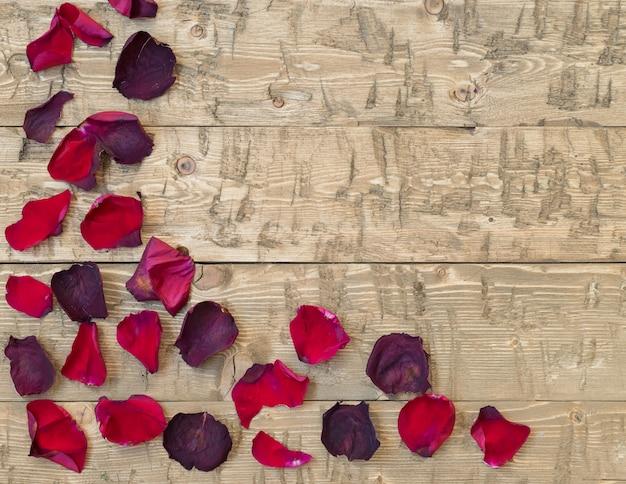 Lindas pétalas de rosa no vintage rústico. tábuas de madeira velhas. Foto Premium