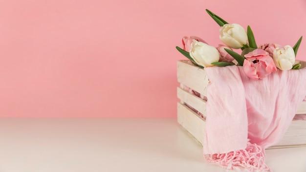 Lindas tulipas e cachecol na caixa de madeira na mesa branca contra um fundo rosa Foto gratuita